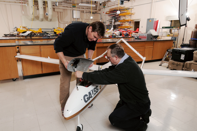 Mike Heiges, kneeling, and Warren Lee install a sensor package on GTRI's flying UAV test bed, GAUSS.Georgia Tech Research Institute