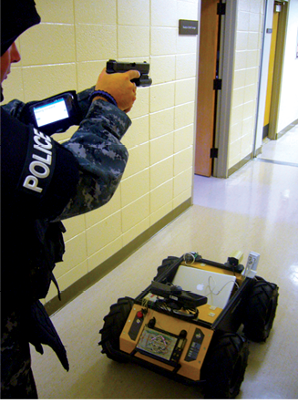 Starkville, MS Officer using an Android device to receive messages and images from the Clearpath Husky robot for determining the robot's intent for upcoming movements.