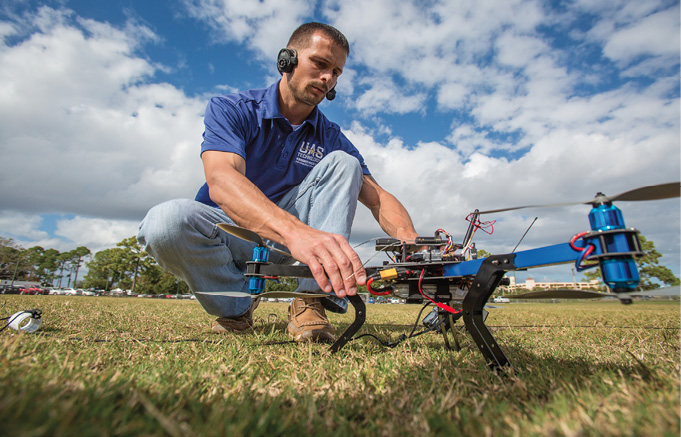 Embry-Riddle UAS club member prepares for a tethered flight with a quadcopter.