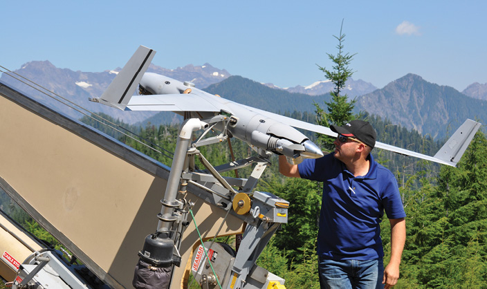 Insitu Rapid Response Team member Bronson Ignacio prepares ScanEagle for flight. Insitu