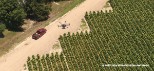 A multi-rotor drone hovering over crops